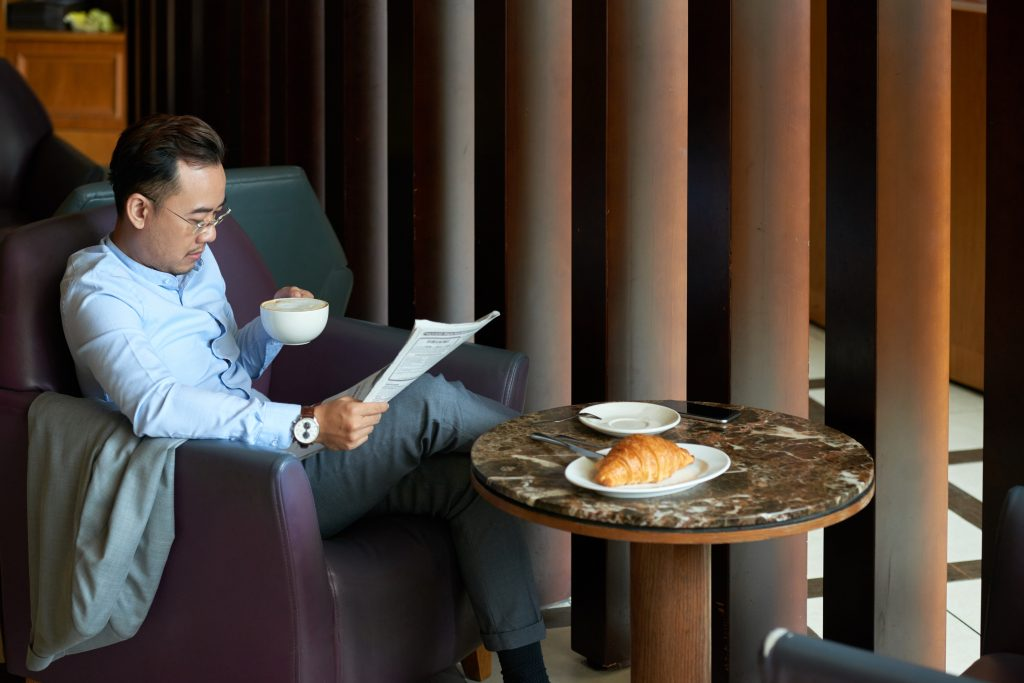 Successful Asian man enjoying cappuccino in restaurant and reading newspaper