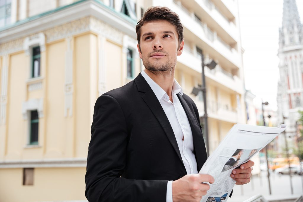 Handsome young businessman with newspaper standing on the street