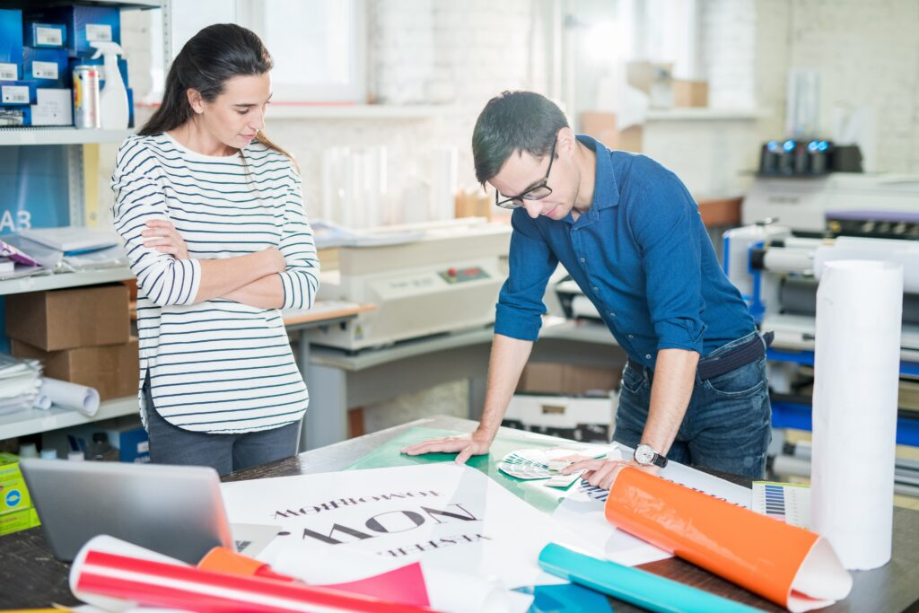 Confident young specialists standing at table full of various types of paper and discussing color palette while going to print banner in advertising company office