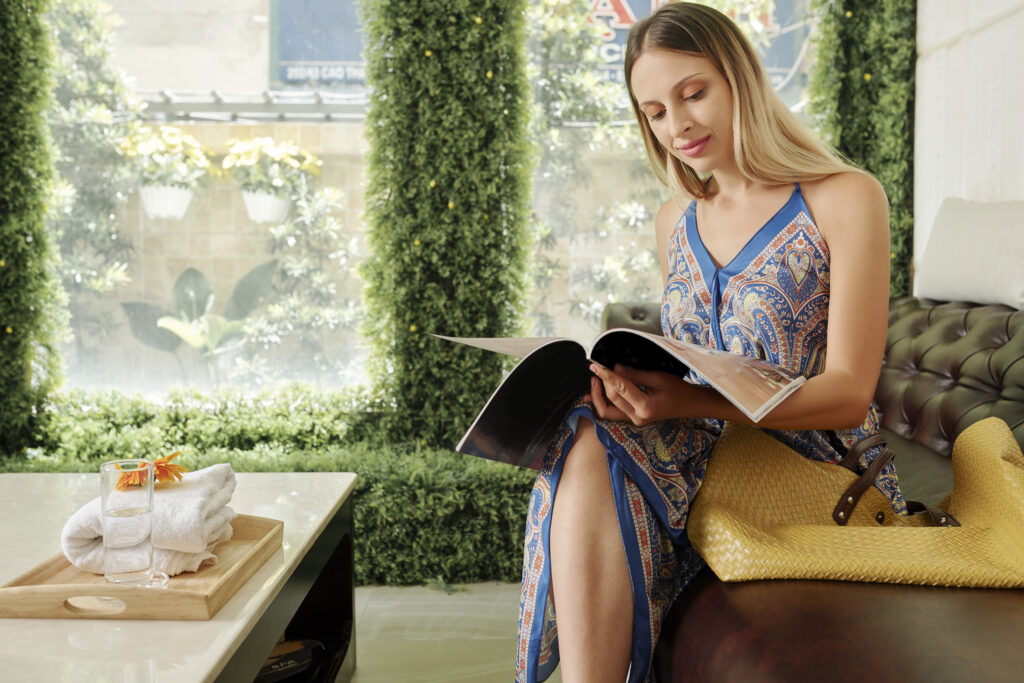Attractive young Caucasian woman reading magazine when waiting in lobby of spa salon or resort